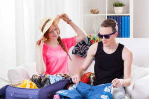 young couple packing for vacation
