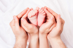 hands of parents concerned barefoot baby